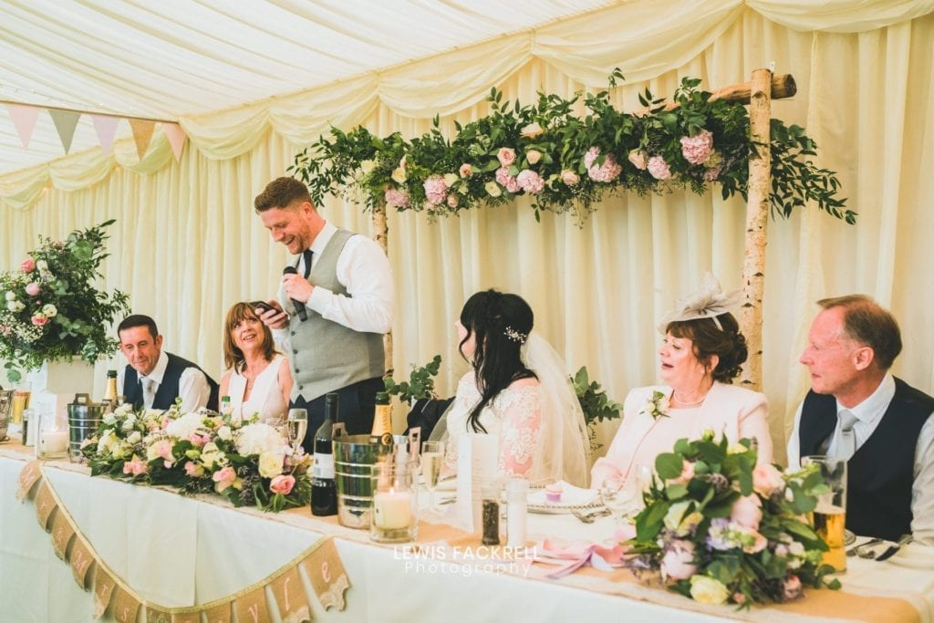 Weddings at South Wales golf resort - Man reading a speech in a decorative wedding venue