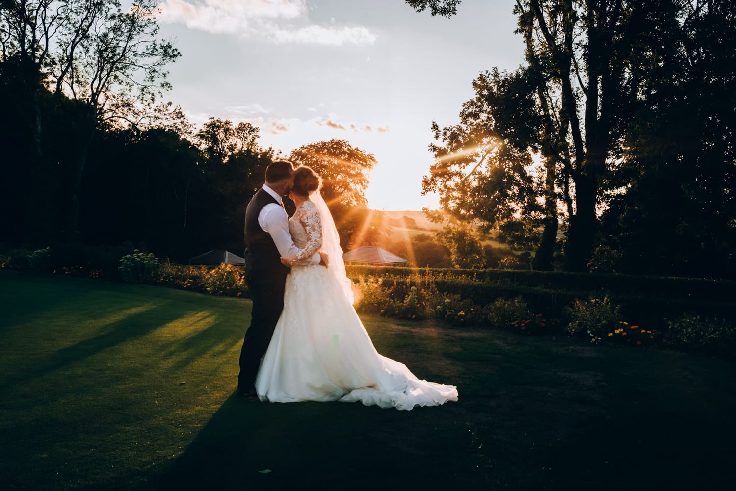 Cottrell Park Golf Resort, wedding venue in South Wales - bridal couple standing in front of sunset
