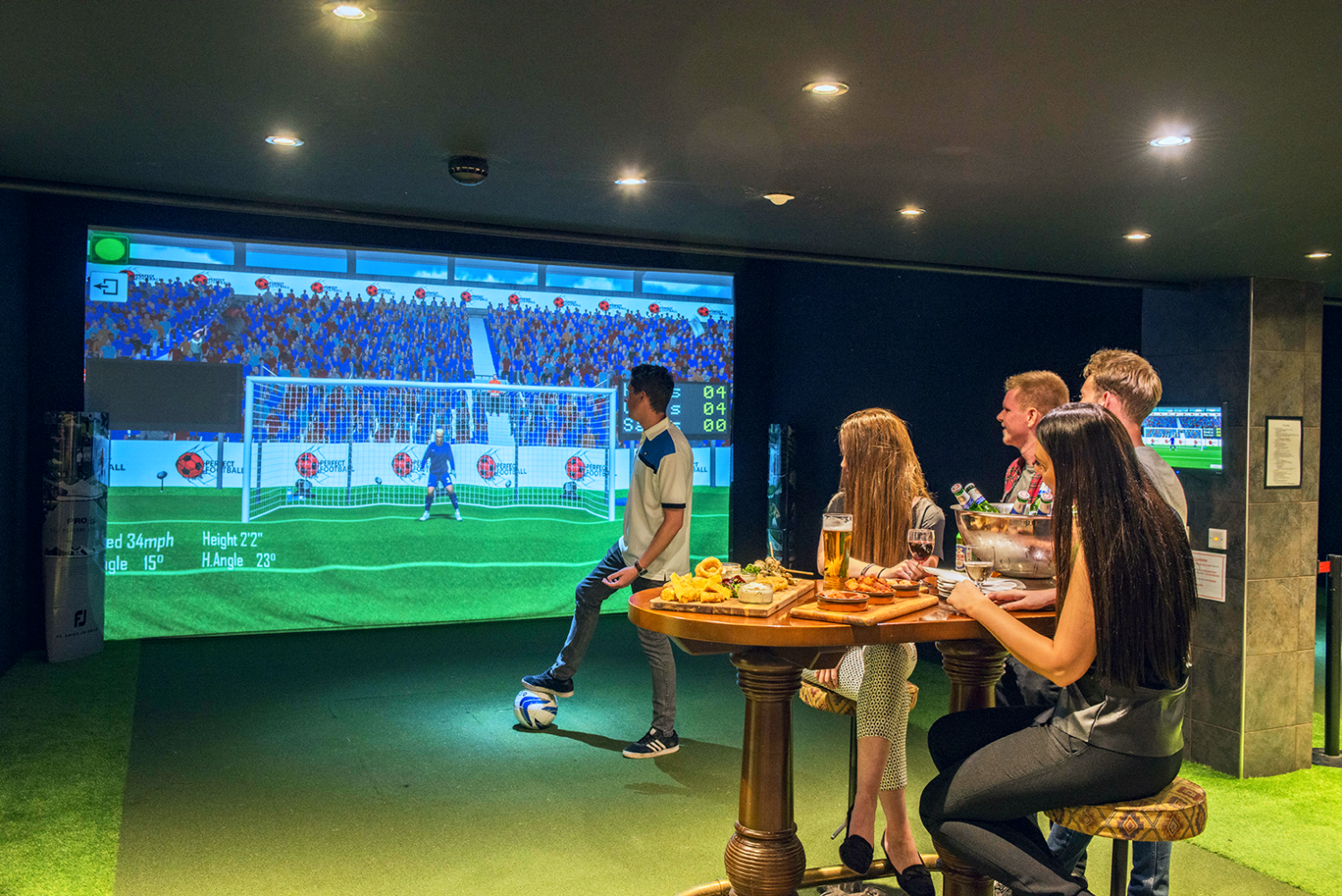 Things to do in Cardiff - Golf simulators South Wales - A group of teenagers eating pub grub as they watch friend play with the sport simulator