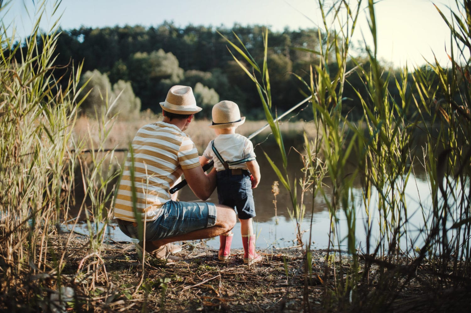 Things to do in Cardiff, family days out - Mature father fishing with his toddler beside a lake