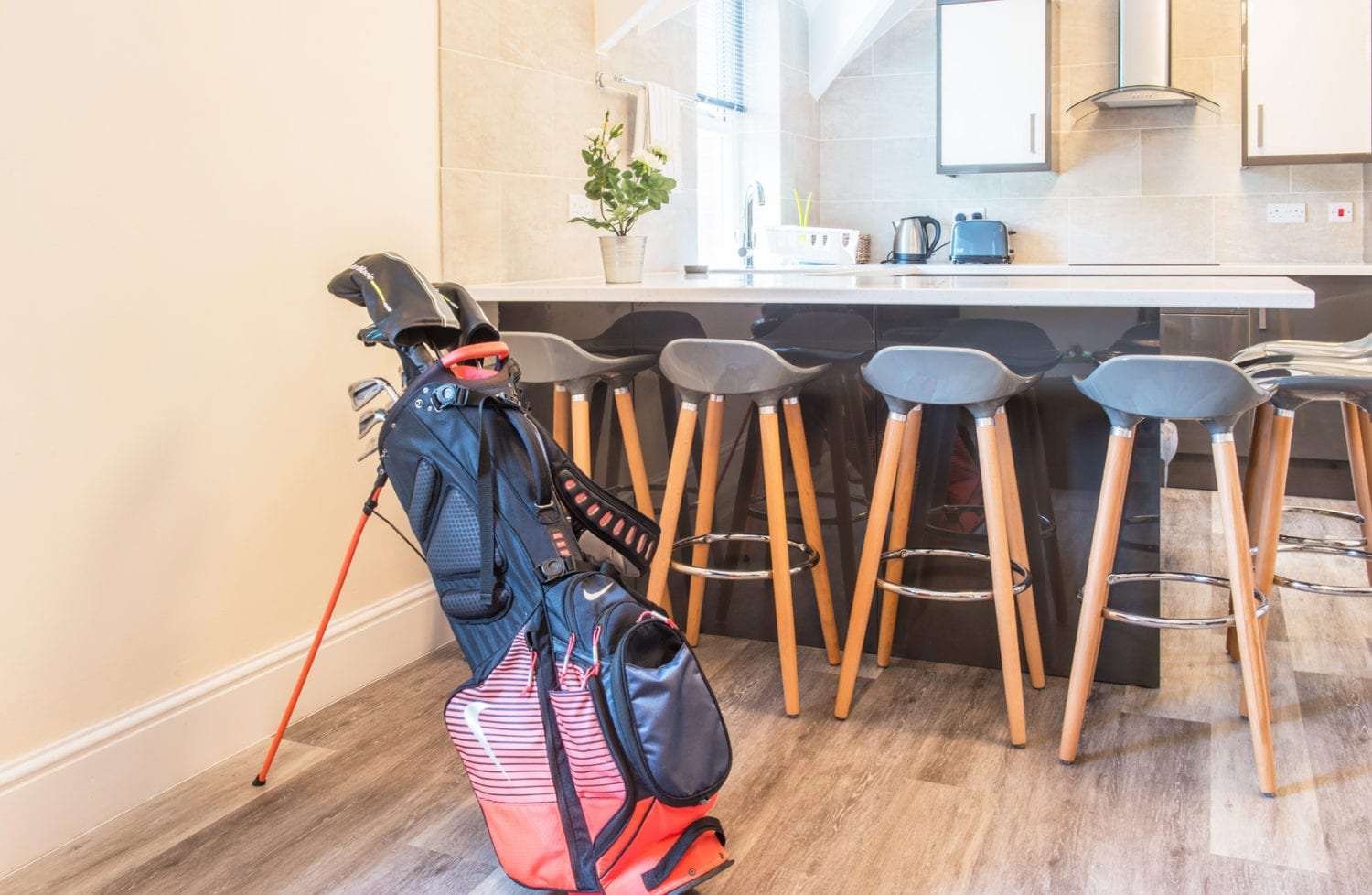 Accommodation at the golf resort in South Wales - A bag of golf clubs placed in a communal kitchen and living room area